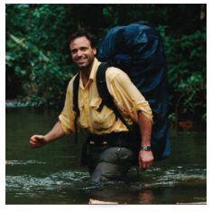 man crossing river wearing long-sleeve hiking shirt